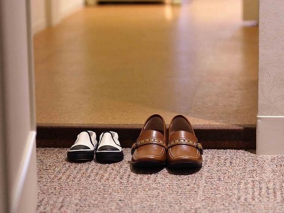 玄関スペースで靴を脱ぐ清潔なお部屋